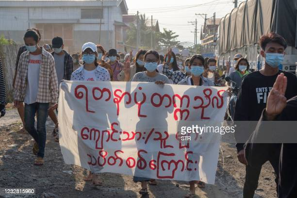 Protesters hold a banner as they march during a demonstration against the military coup in Mandalay on May 11, 2021.
