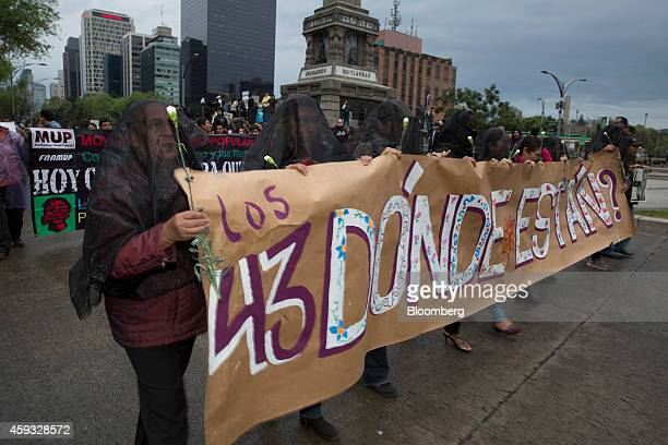 Protesters hold a banner as they march toward the central square known as the Zocalo to protest at the government's response to the mass...