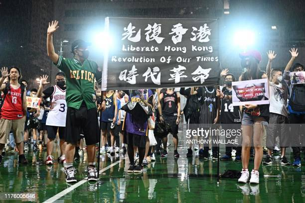 Protesters hold a banner as they shout slogans at the Southorn Playground in Hong Kong on October 15 during a rally in support of NBA basketball...