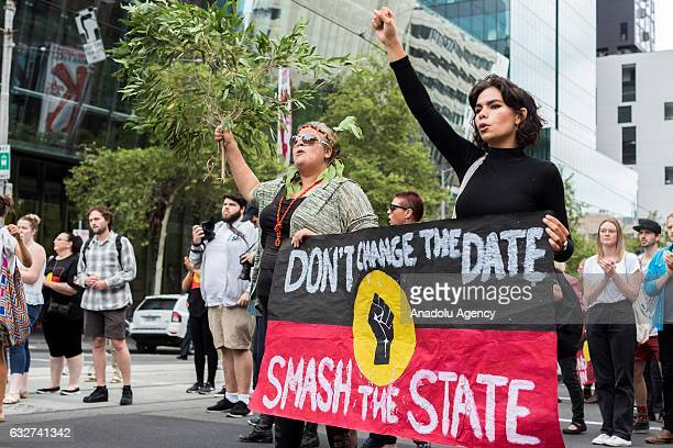 Protesters hold a banner as they shout slogans during a protest organized by Aboriginal rights activists on Australia Day in Melbourne Australia on...