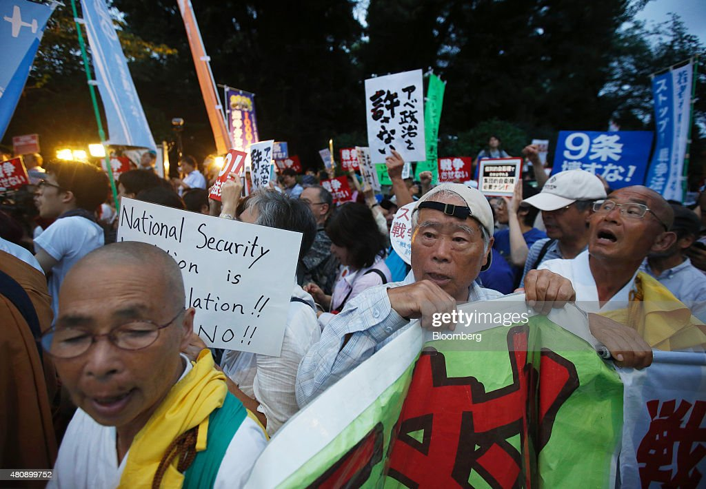 Protesters hold a banner as they take part in a rally against the security bills outside the National Diet building in Tokyo, Japan, on Thursday, July 16, 2015. Japanese Prime Minister Shinzo Abe's security bills passed parliament's lower house Thursday after a night of noisy protests, as his push to expand the role of the military risks further eroding his public support. Photographer: Tomohiro Ohsumi/Bloomberg via Getty Images