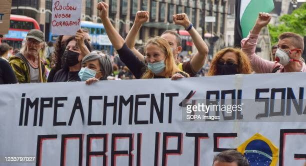 Protesters hold a banner calling for the impeachment of Bolsonaro during the demonstration. Protesters gathered at Parliament Square in protest...