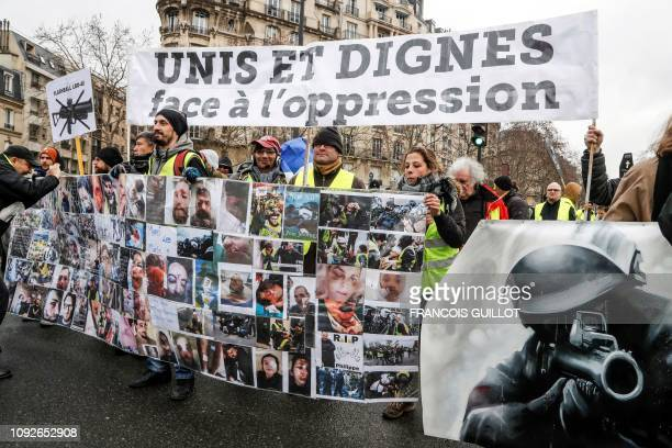 Protesters hold a banner depicting injured people, next to a drawing of a police officer pointing a 40-millimetre rubber defensive ball launcher LBD,...
