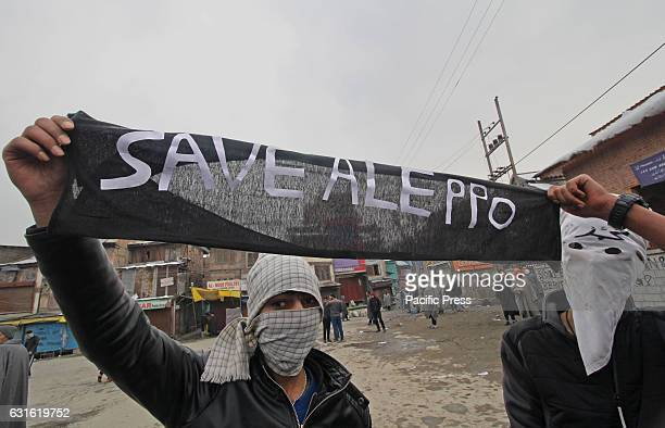 Protesters hold a banner in solidarity with the people of Aleppo Syria during a demonstrationClashes erupted in many parts of Srinagar against the...