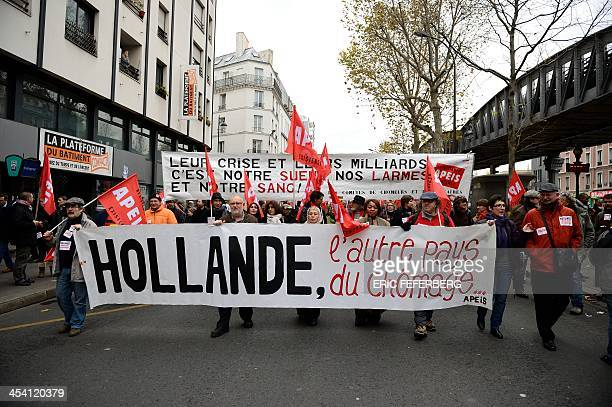 Protesters hold a banner reading 'Hollande the other country of unemployment' as they take part in a demonstration against unemployment on December 7...