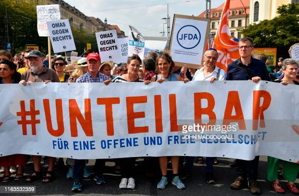 """Protesters hold a banner reading """"Indivisible - For an open and free society"""" as they take part in a demonstration titled """"Unteilbar"""" against..."""