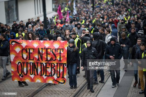 Protesters hold a banner reading It's only the beginning as they attend during a demonstration marking the first anniversary of the yellow vest...