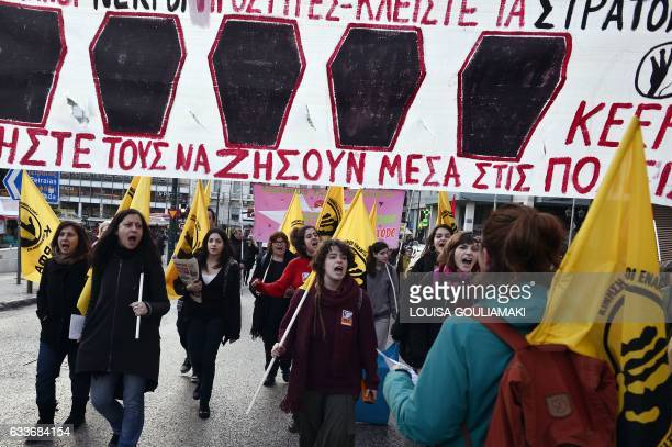 Protesters hold a banner reading 'let them live inside the cities' in Athens on February 3 as they protest against the Greek migrant camps conditions...