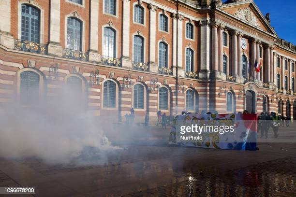 Protesters hold a banner reading 'Liberty Equality Fraternity' near tear gas canisters in front of the townhall of Toulouse the Capitole Act XIII...