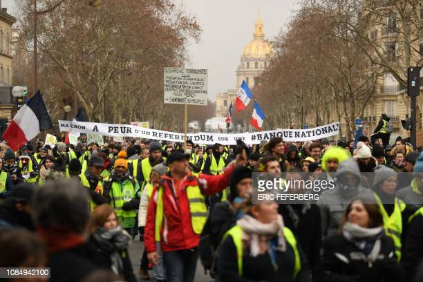 """Protesters hold a banner reading """"Macron is afraid of a referendum on a National Bank"""" as they march near the Hotel des Invalides during an..."""