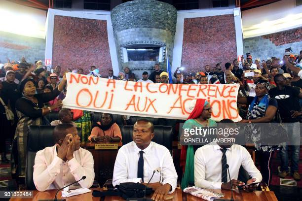 Protesters hold a banner reading 'No to the conference Yes to actions' as they dance and shout slogans after entering the Mayotte Departmental...