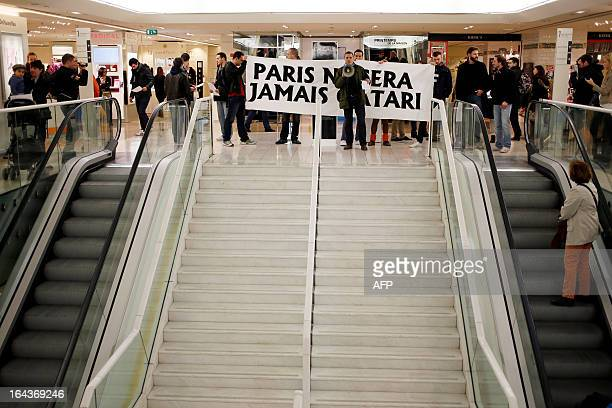"""Protesters hold a banner reading """"Paris will never be Qatar"""" during a demonstration by the French far-right organization Bloc Identitaire to protest..."""