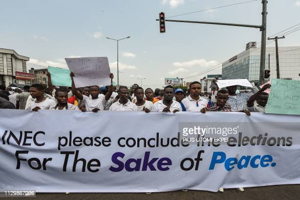 Protesters hold a banner reading Please conclude the elections for the sake of peace during a demonstration against the suspension of governorship...