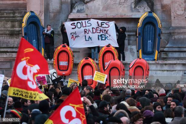 Protesters hold a banner reading 'Under the rafts the sea' as they stand next to inflatable dinghies on the Place SaintMichel in Paris on February 21...
