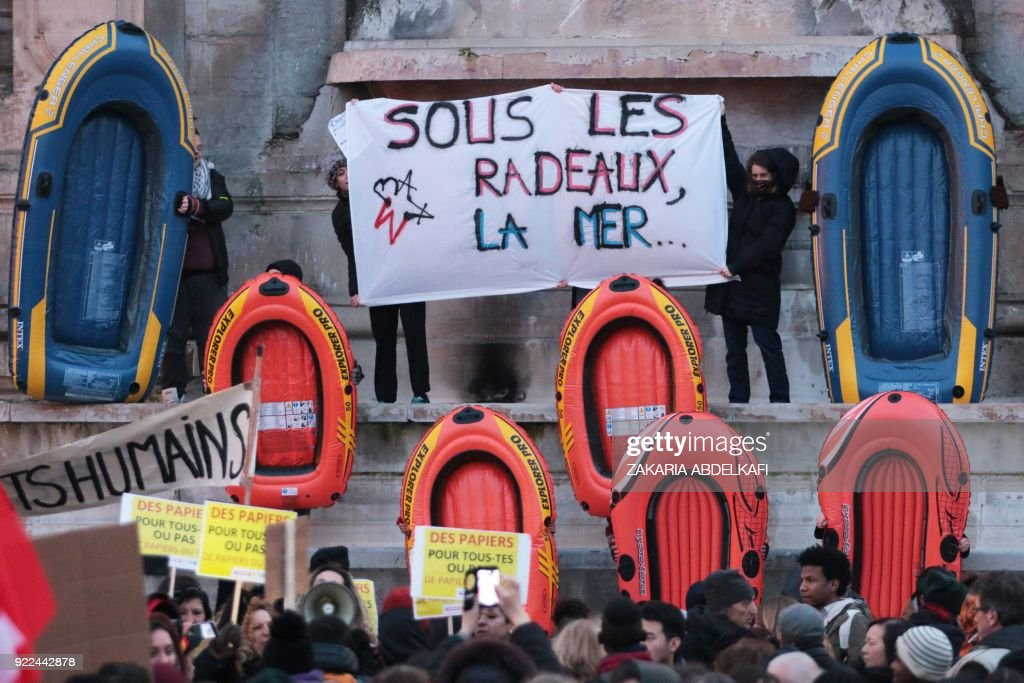 Protesters hold a banner reading 'Under the rafts, the sea' as they stand next to inflatable dinghies on the Place Saint-Michel in Paris on February 21, 2018, during a demonstration against the Fre...