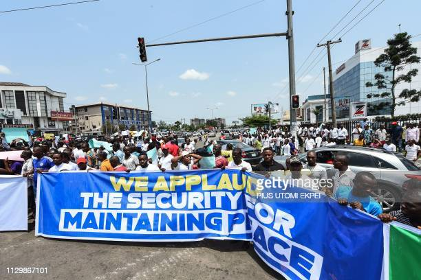 Protesters hold a banner reading 'We applaud the security for maintaining peace' during a demonstration against the suspension of governorship...