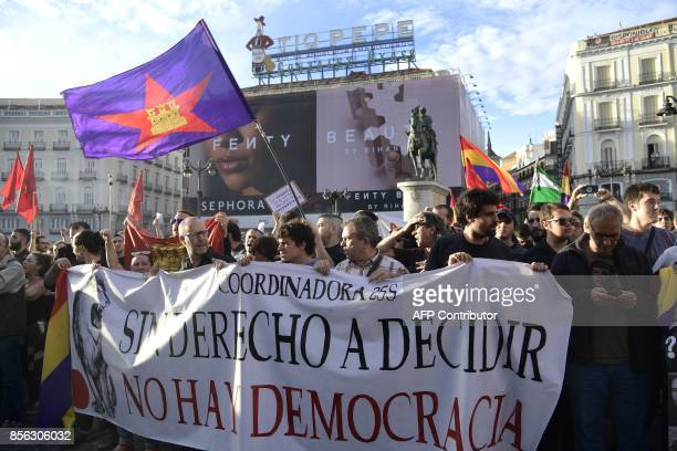 Protesters hold a banner reading 'Without the right to decide there's no democracy' as they gather at Puerta del Sol square during a demonstration in...