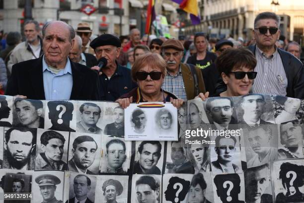 Protesters hold a banner with pictures of missing people during the Spanish dictatorship of Francisco Franco as they take part in protest in Madrid...
