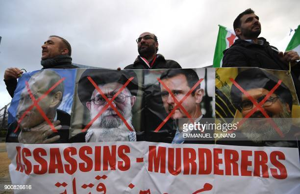 Protesters hold a banner with the crossedout portraits of Russian President Vladimir Putin Iranian supreme leader Ayatollah Ali Khamenei Syrian...