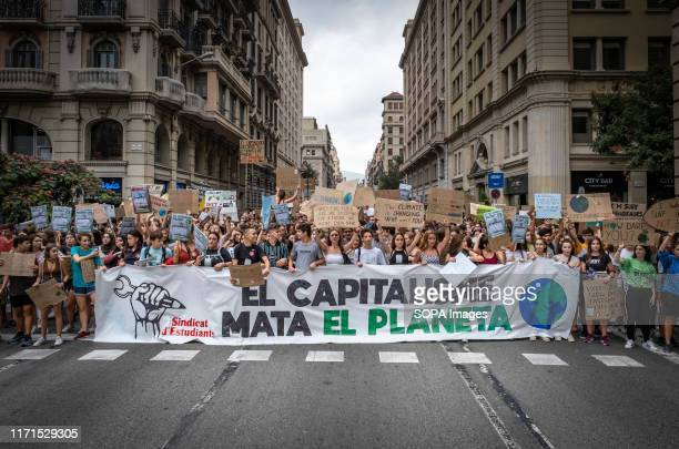 Protesters hold a banner with the slogan Capitalism kills the planet and placards during the demonstration More than 1000 students convened by the...