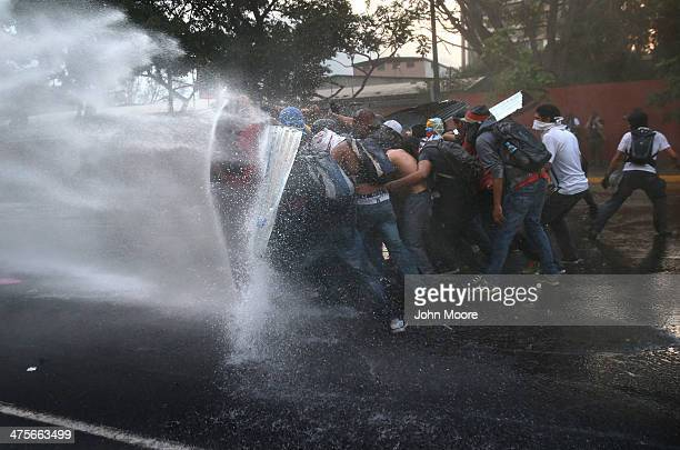 Protesters hold a barricade against a water canon fired by the Venezuelan national guard during an antigovernment demonstration on February 27 2014...