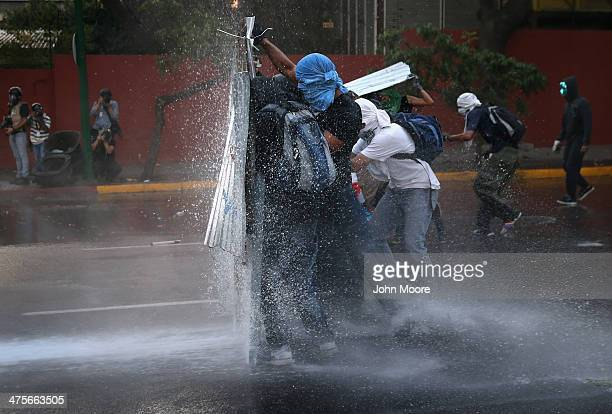 Protesters hold a barricade against a water canon fired by the national guard during an antigovernment demonstration on February 27 2014 in Caracas...