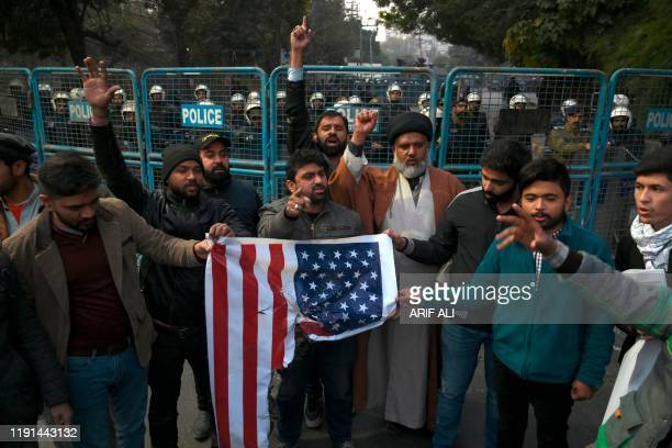 Protesters hold a burned US flag as they shout slogans during a demonstration near the US consulate following a US airstrike that killed top Iranian...