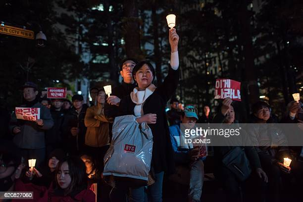 Protesters hold a candlelight vigil calling for the resignation of South Korea's President Park GeunHye in Seoul on November 3 2016 A snowballing...