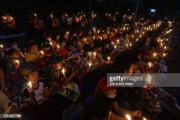 Protesters hold a candlelight vigil outside the US Embassy during a demonstration against the military coup in Yangon on February 21, 2021.