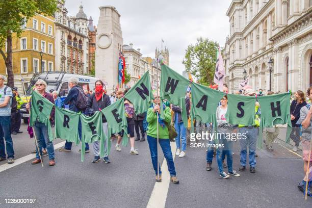 Protesters hold a clothes line with letters on the attached shirts spelling out 'Greenwash' during the demonstration outside Downing Street....