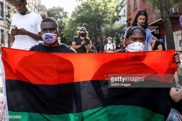 Protesters hold a flag while wearing face masks during the demonstration. Protests continue against police brutality and racial injustice in New York...