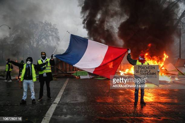 Protesters hold a French flag near a burning barricade during a protest of Yellow vests against rising oil prices and living costs, on December 1,...