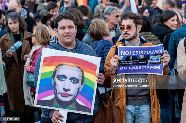 Protesters hold a 'gay clown' poster of Russian President Vladimir Putin and another with the sign reading in Italian and Cyrillic 'we exist' during...