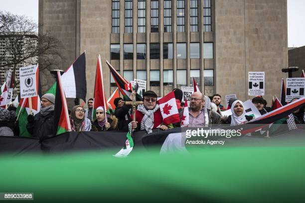Protesters hold a giant Palestinian flag as they walk across University Avenue in front of the US consulate during a demonstration against the recent...
