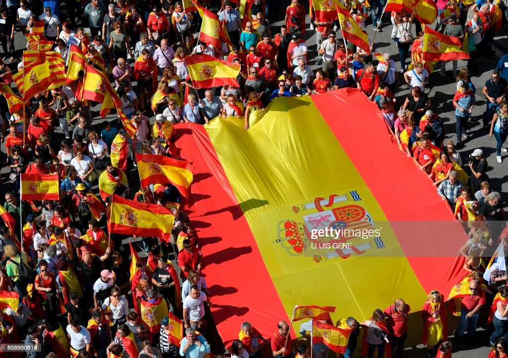 TOPSHOT - Protesters hold a giant Spanish flag during a demonstration called by 'Societat Civil Catalana' (Catalan Civil Society) to support the unity of Spain on October 8, 2017 in Barcelona. Spain braced for more protests despite tentative signs that the sides may be seeking to defuse the crisis after Madrid offered a first apology to Catalans injured by police during their outlawed independence vote. /