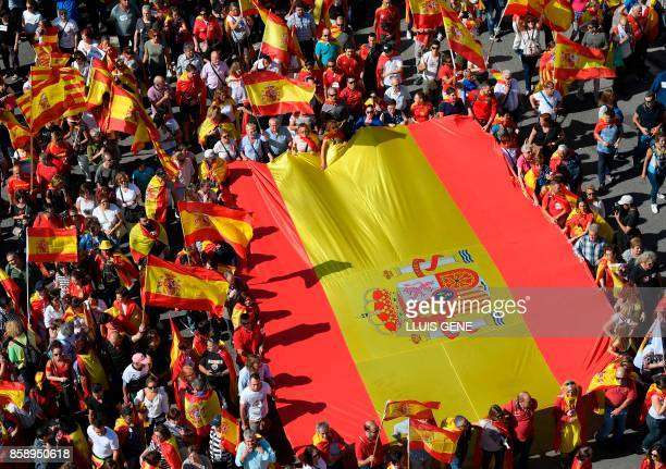 TOPSHOT Protesters hold a giant Spanish flag during a demonstration called by 'Societat Civil Catalana' to support the unity of Spain on October 8...