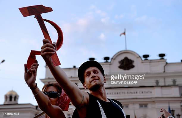 Protesters hold a hammer and a sickle as they reenact famous Soviet sculpture 'Worker and Kolkhoz Woman' during an antigovernment demonstration in...