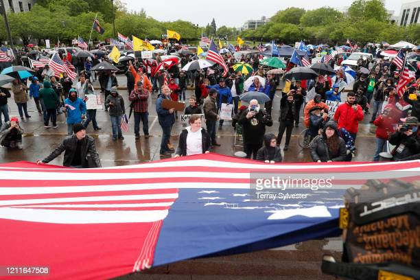 Protesters hold a large American Flag at the ReOpen Oregon Rally on May 2 2020 in Salem Oregon Demonstrators gathered at the state capitol to demand...
