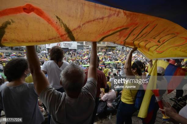 Protesters hold a large Colombian flag at Loma de la Cruz as the march passes through Cruz de la Loma towards Universidad del Valle of the march at...