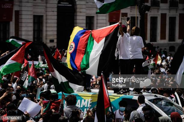 Protesters hold a Palestinian flag along with a Colombian flag as they sing songs of support for Palestine and against Israel in Madrid, Spain, on...
