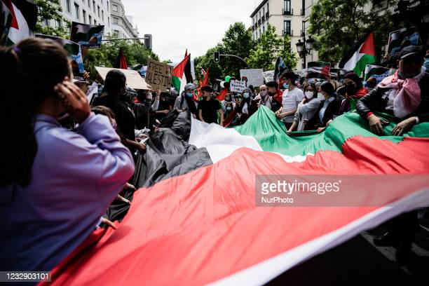 Protesters hold a Palestinian flag as they sing songs of support for Palestine and against Israel in Madrid, Spain, on May 15 on the occasion of the...