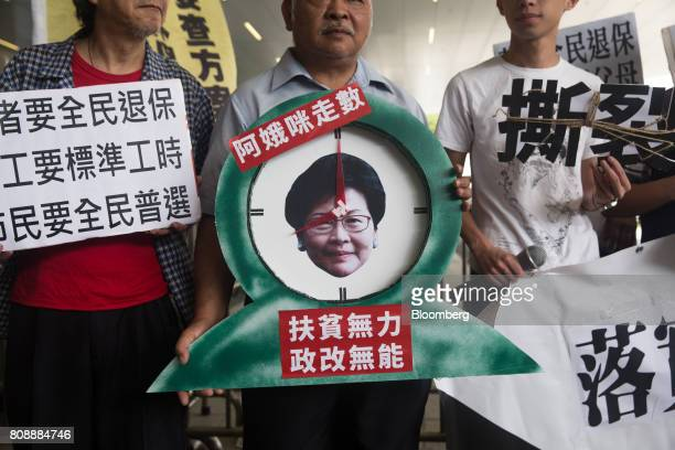 Protesters hold a placard critical of Hong Kong Chief Executive Carrie Lam during a demonstration outside the Legislative Council building in Hong...
