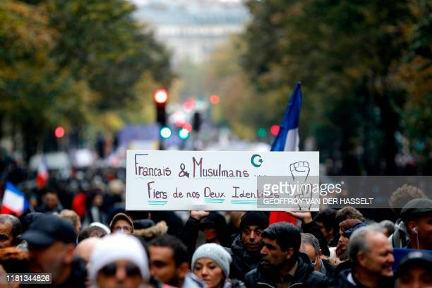 "Protesters hold a placard reading ""French and muslims, proud of our identities"" as they march in Paris to protest against Islamophobia, on November..."