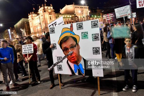 Protesters hold a poster bearing a portrait of Serbian President Aleksandar Vucic with Pinocchio's nose during a demonstration against the Serbian...
