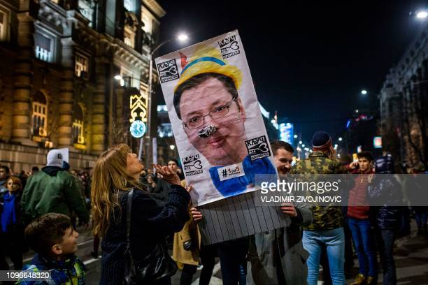 Protesters hold a poster depicting Serbian President Aleksandar Vucic during a demonstration against Serbian President Aleksandar Vu?i? in Belgrade...