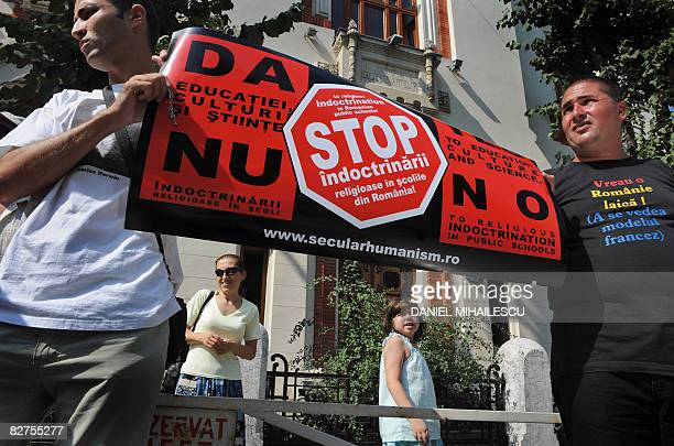 Protesters hold a poster reading in Romanian and English Don't force them The pupils have the right to choose and Stop the religious indoctrination...