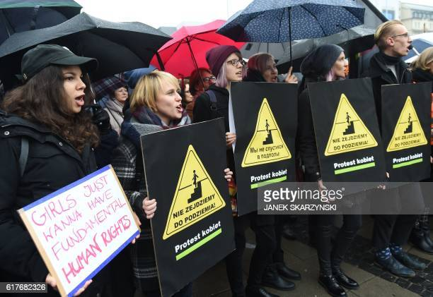 Protesters hold a posters and raise umbrellas as a symbol of their protest during a rally in Warsaw on October 24 2016 Polish women have again donned...