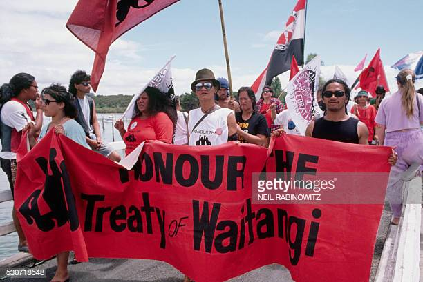 Protesters hold a rally in protest during Queen Elizabeth's visit to New Zealand Their banner reads HONOUR THE TREATY of WAITANGI which refers to an...