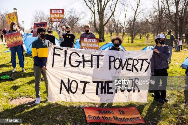 Protesters hold a sign reading, Fight Poverty Not the Poor. A coalition of Bloomington community members, activists, and Indiana University students...