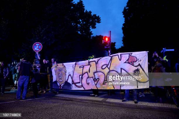 Protesters hold a sign reading 'Fuck G20' and showing a drawing of the USPresident Trump in St Pauli in Hamburg Germany 04 July 2017 Hundreds of...